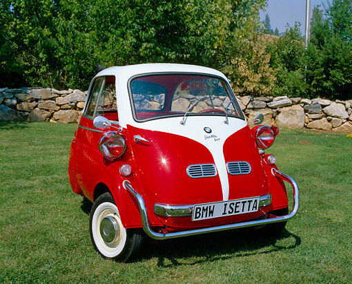 AUT 01 RK0171 02 © Kimball Stock 1958 BMW Isetta Red And White 3/4 Front View On Grass Rock Fence