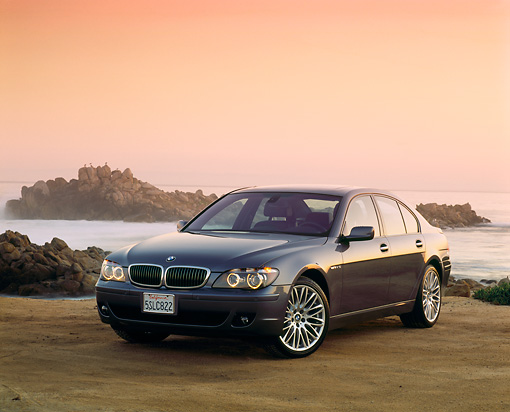 AUT 01 RK0229 01 © Kimball Stock 2006 BMW 760i Blue 3/4 Front View On Sand By Ocean At Dusk