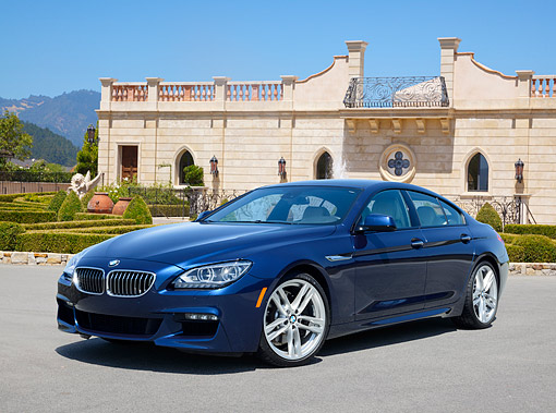 AUT 01 RK0355 01 © Kimball Stock 2013 BMW 640i Gran Coupe Blue 3/4 Front View On Pavement By Building