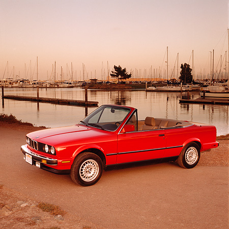 AUT 01 RK0011 02 © Kimball Stock 1989 BMW Convertible Red Side 3/4 View On Dirt By Water At Dusk