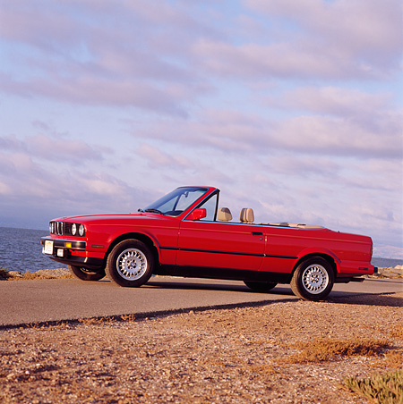 AUT 01 RK0015 01 © Kimball Stock 1989 BMW Convertible Red Low 3/4 Front View On Pavement Cloudy Sky