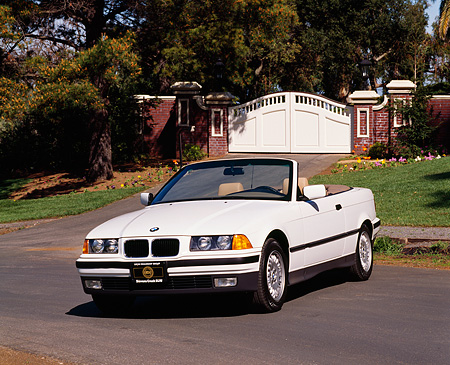AUT 01 RK0028 07 © Kimball Stock 1994 BMW 325 Convertible White 3/4 Front View On Pavement By Gate