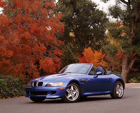 AUT 01 RK0035 02 © Kimball Stock 1999 BMW M Roadster Z3 Convertible Blue Low 3/4 Front View On Pavement By Fall Colored Trees