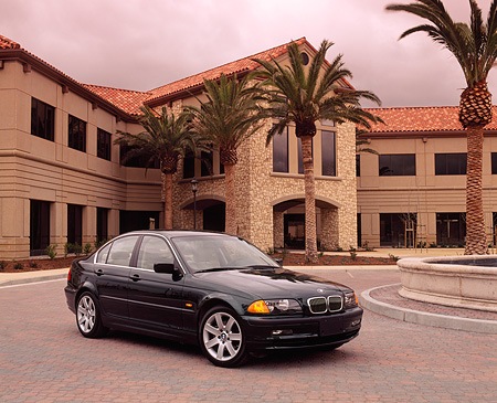 AUT 01 RK0078 03 © Kimball Stock 1999 BMW 328i Green 3/4 Front View On Pavement By Building And Palm Trees Filtered