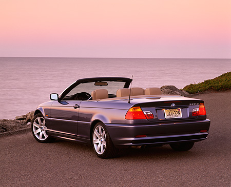 AUT 01 RK0105 02 © Kimball Stock 2001 BMW 323Ci Convertible Blue 3/4 Rear View On Pavement By Water At Dusk