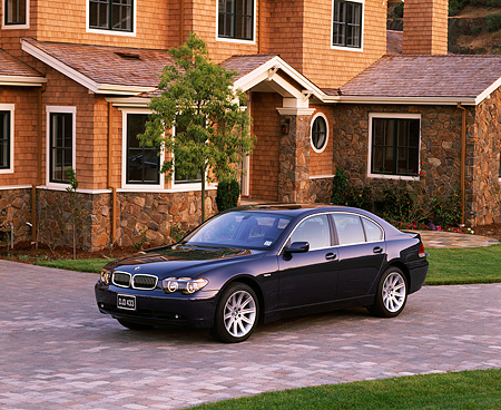 AUT 01 RK0132 01 © Kimball Stock 2002 BMW 745i Blue 3/4 Side View On Driveway By House