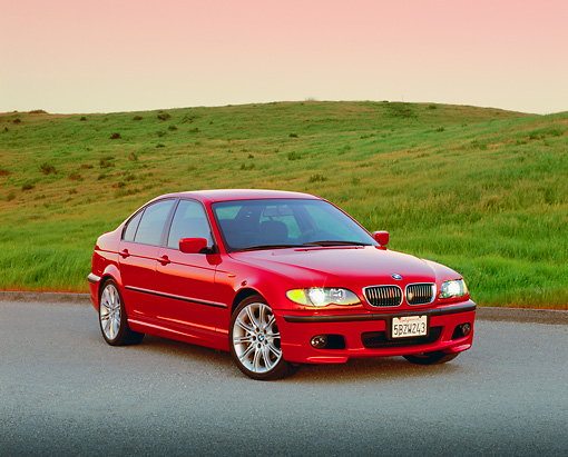 AUT 01 RK0177 01 © Kimball Stock 2003 BMW 330i Sport Sedan Red 3/4 Front View On Pavement By Grass Hill Filtered