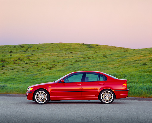 AUT 01 RK0181 06 © Kimball Stock 2003 BMW 330i Sport Sedan Red Profile On Pavement By Grass Hill Filtered