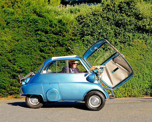 AUT 01 RK0204 01 © Kimball Stock 1958 BMW Isetta 300 Light Blue Door Open Profile View On Pavement By Shrubs