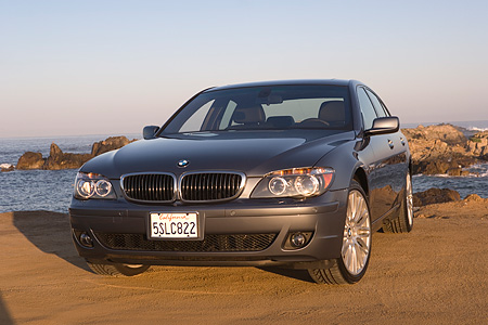 AUT 01 RK0233 01 © Kimball Stock 2006 BMW 760i Gray Low 3/4 Front View On Sand By Ocean And Rocks