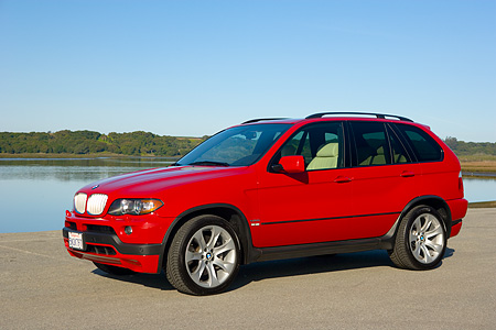 AUT 01 RK0244 01 © Kimball Stock 2006 BMW X5 Red 3/4 Side View On Pavement By Water Blue Sky