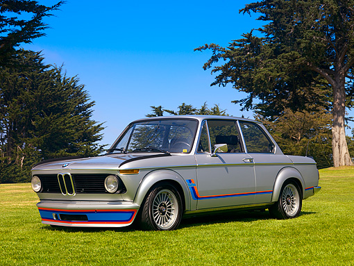 AUT 01 RK0280 01 © Kimball Stock 1975 BMW 2002 Factory Turbo Silver Low 3/4 Front View On Grass By Trees