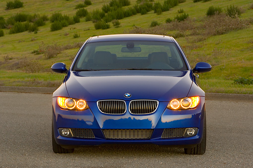 AUT 01 RK0289 01 © Kimball Stock 2007 BMW 335i Coupe Blue Head On View On Pavement By Hills