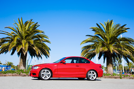 AUT 01 RK0318 01 © Kimball Stock 2008 BMW 135i Red 3/4 Front View By Palm Trees Blue Sky