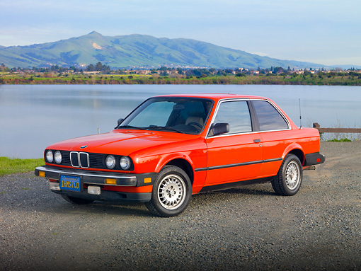 AUT 01 RK0335 01 © Kimball Stock 1984 BMW 318i Red 3/4 Front View On Pavement By Hills And Lake