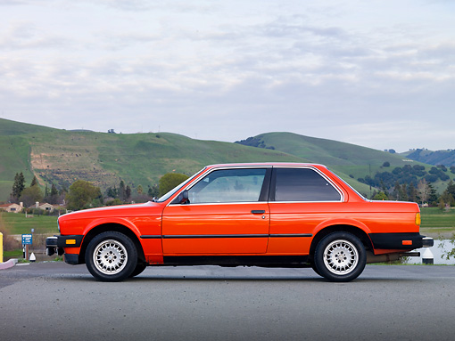 AUT 01 RK0340 01 © Kimball Stock 1984 BMW 318i Red Profile View On Pavement By Hills