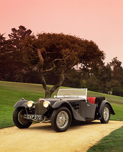 AUT 02 RK0045 12 © Kimball Stock 1937 Bugatti Convertible Black 3/4 Front View On Sand By Grass And Tree Pebble Beach