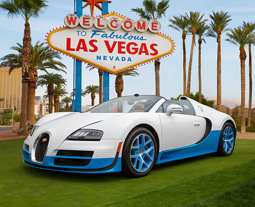 AUT 02 RK0150 01 © Kimball Stock Bugatti Veyron 16.4 Grand Sport Vitesse SE White And Blue 3/4 Front View On Grass By Las Vegas Sign