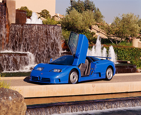 AUT 02 RK0010 07 © Kimball Stock 1994 Bugatti EB110 GT Coupe Blue Door Open 3/4 Side View By Water Fountain