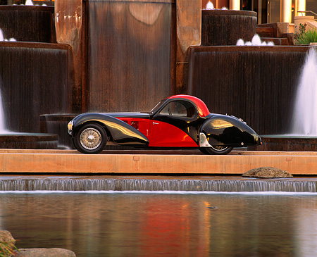 AUT 02 RK0020 01 © Kimball Stock 1937 Bugatti Atalante Type 57SC Coupe Black And Red Profile By Water Fountain