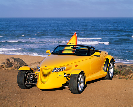 AUT 03 RK0008 08 © Kimball Stock 1999 Plymouth Prowler Roadster Yellow Front 3/4 View On Sand By Ocean