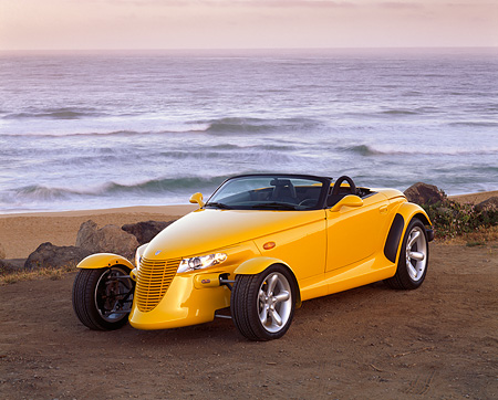 AUT 03 RK0011 03 © Kimball Stock 1999 Plymouth Prowler Yellow Roadster 3/4 Front View On Sand By Ocean