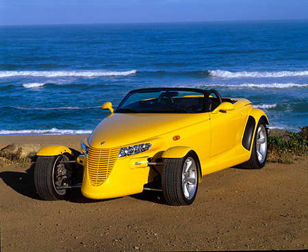 AUT 03 RK0012 07 © Kimball Stock 1999 Plymouth Prowler Roadster Yellow 3/4 Front View On Beach Ocean Background