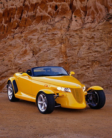 AUT 03 RK0015 06 © Kimball Stock 1999 Plymouth Prowler Roadster Yellow 3/4 Front View On Sand Against Rock