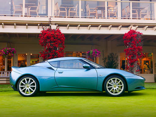 AUT 04 BK0002 01 © Kimball Stock 2013 Lotus Evora Coupe Blue Profile View On Grass By Building