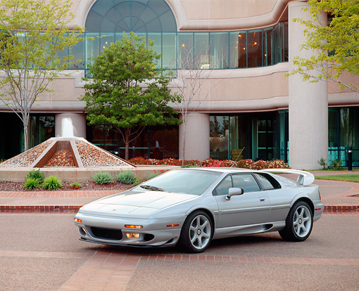 AUT 04 RK0045 01 © Kimball Stock 1999 Lotus Esprit V8 Silver Front 3/4 View On Pavement By Water Fountain