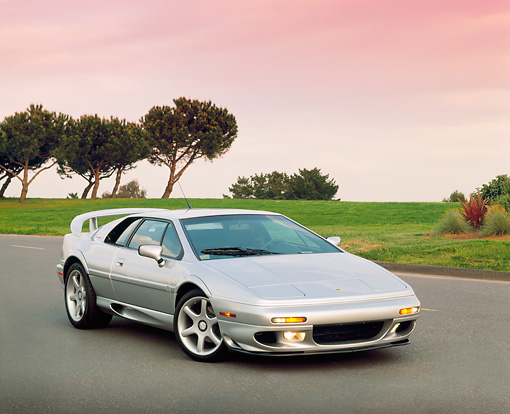 AUT 04 RK0046 03 © Kimball Stock 1999 Lotus Esprit V8 Silver Front 3/4 View On Pavement By Trees At Dusk