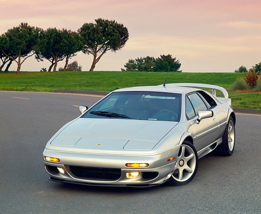 AUT 04 RK0047 01 © Kimball Stock 1999 Lotus Esprit V8 Silver Front 3/4 View On Pavement By Trees At Dusk