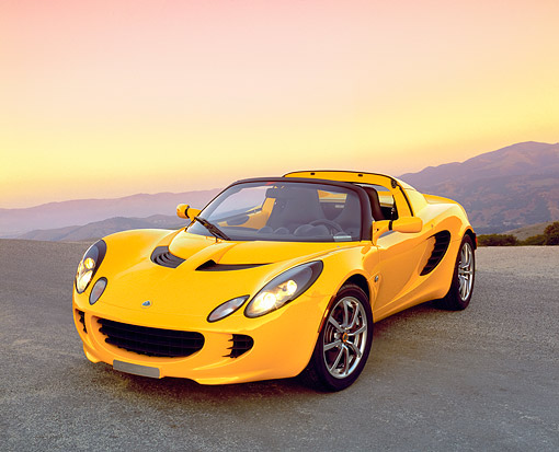 AUT 04 RK0120 01 © Kimball Stock 2003 Lotus Elise Yellow 3/4 Front View On Pavement Hill Mountains Background