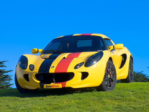 AUT 04 RK0150 01 © Kimball Stock 2005 Lotus Elise Yellow Sunburst Red And Black Stripes Front 3/4 View On Grass Blue Sky