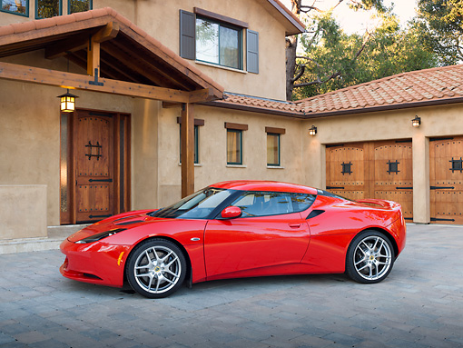 AUT 04 RK0181 01 © Kimball Stock 2013 Lotus Evora Red 3/4 Side View On Brick By House