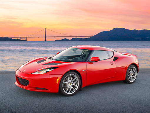 AUT 04 RK0183 01 © Kimball Stock 2013 Lotus Evora Red 3/4 Front View On Pavement By Bay And Bridge At Sunset
