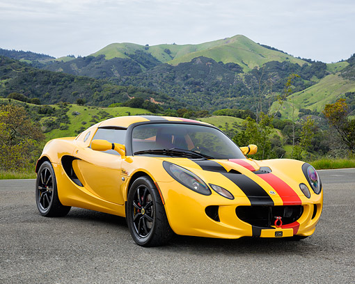 AUT 04 RK0200 01 © Kimball Stock 2010 Lotus Elise Yellow 3/4 Front View By Mountains And Trees