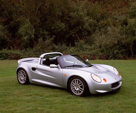 AUT 04 RK0077 01 © Kimball Stock 2002 Lotus Elise Sunspeed Spider Silver 3/4 Side View On Grass Trees Background