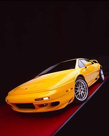 AUT 04 RK0087 05 © Kimball Stock 2002 Lotus Esprit Turbo V8 25th Anniversary Edition Yellow Wide Angle 3/4 Front View On Red Floor Studio