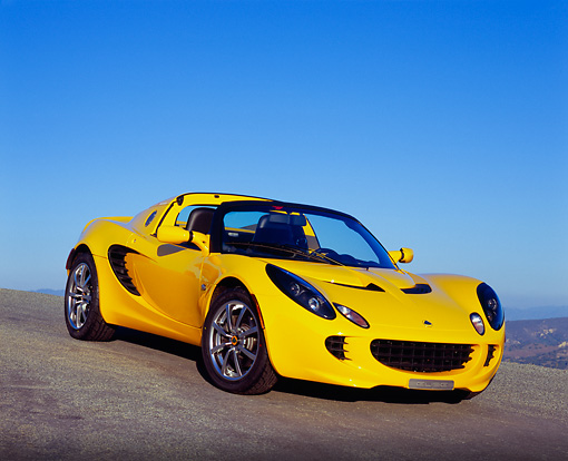 AUT 04 RK0116 02 © Kimball Stock 2003 Lotus Elise Yellow 3/4 Front View On Pavement Hill Blue Sky