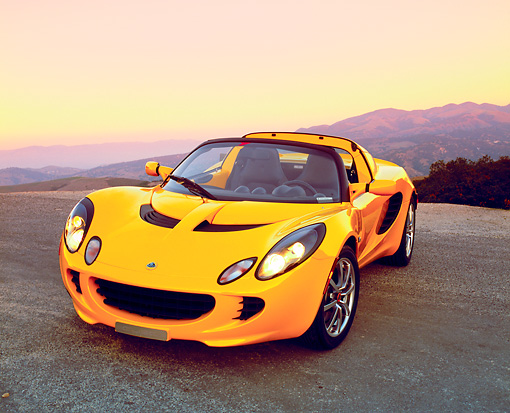 AUT 04 RK0121 03 © Kimball Stock 2003 Lotus Elise Yellow 3/4 Front View On Pavement Mountains Background