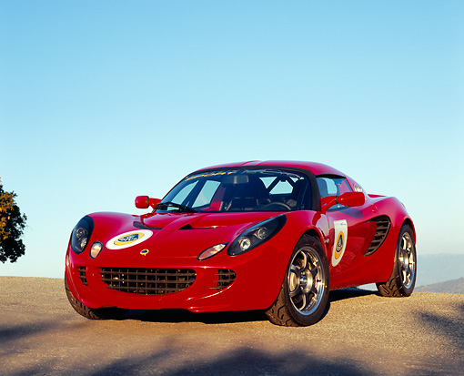 AUT 04 RK0122 01 © Kimball Stock 2005 Lotus Elise Red 3/4 Front View On Pavement Hill Blue Sky