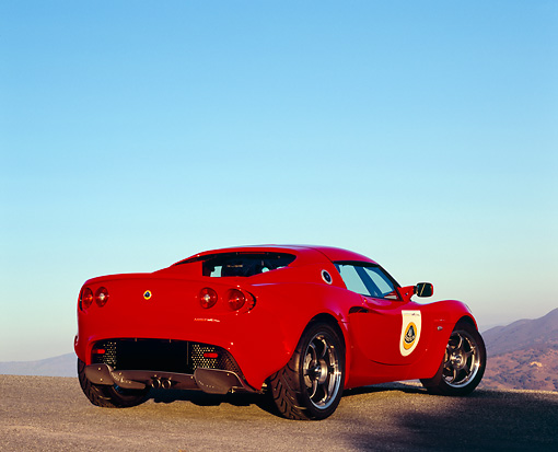 AUT 04 RK0124 02 © Kimball Stock 2005 Lotus Elise Red 3/4 Low Rear View On Pavement Hill Blue Sky