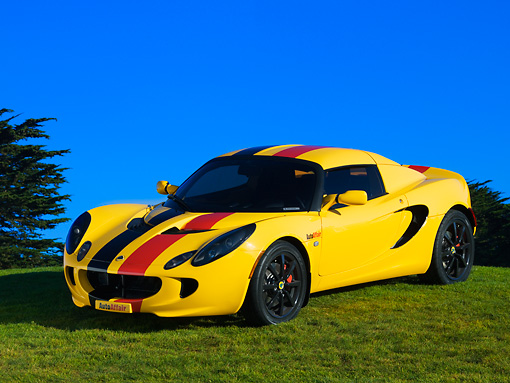 AUT 04 RK0149 03 © Kimball Stock 2005 Lotus Elise Yellow Sunburst Red And Black Stripes Front 3/4 View On Grass Blue Sky