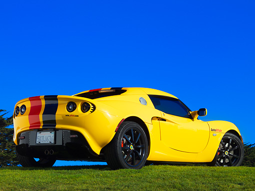 AUT 04 RK0151 01 © Kimball Stock 2005 Lotus Elise Yellow Sunburst Red And Black Stripes Rear 3/4 View On Grass Blue Sky