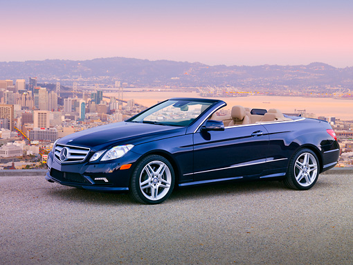AUT 05 BK0009 01 © Kimball Stock 2011 Mercedes-Benz E550 Cabriolet Blue 3/4 Side View On Pavement By San Francisco Skyline