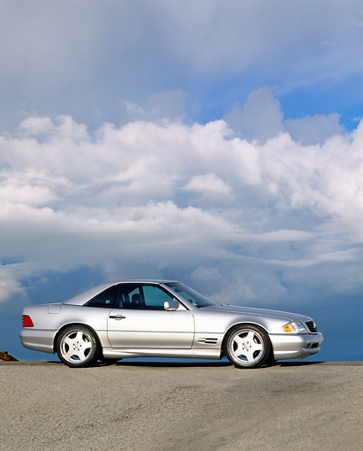 AUT 05 RK0069 05 © Kimball Stock 1997 Mercedes-Benz 500SL Sport Silver 3/4 Side View On Pavement Hill Clouds