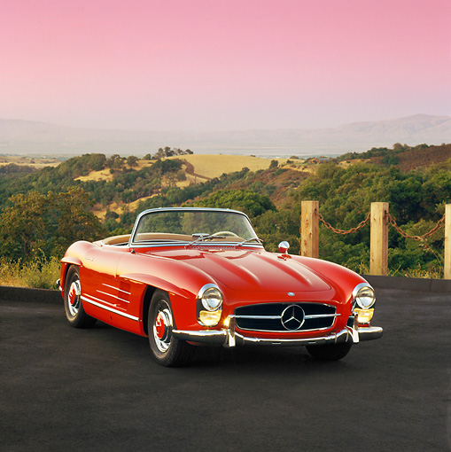 AUT 05 RK0147 04 © Kimball Stock Mercedes-Benz 300SL Convertible Red 3/4 Front View On Pavement By Hills At Dusk