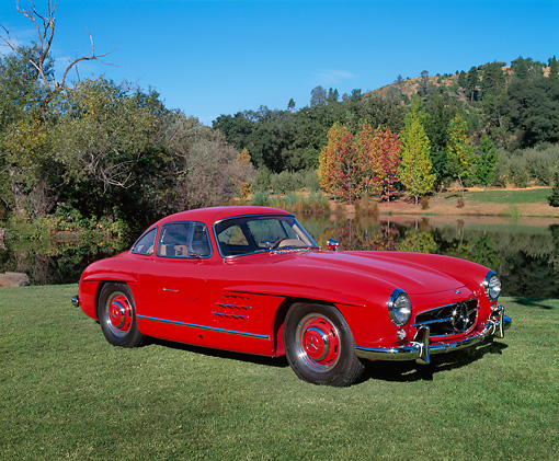 AUT 05 RK0220 03 © Kimball Stock 1955 Mercedes-Benz 300SL Gullwing Coupe Red 3/4 Side View On Grass By Water And Trees