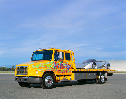 AUT 05 RK0336 06 © Kimball Stock Tow Truck With 1991 Mercedes Lotec C1000 Silver On Bed Airplane Hanger Background